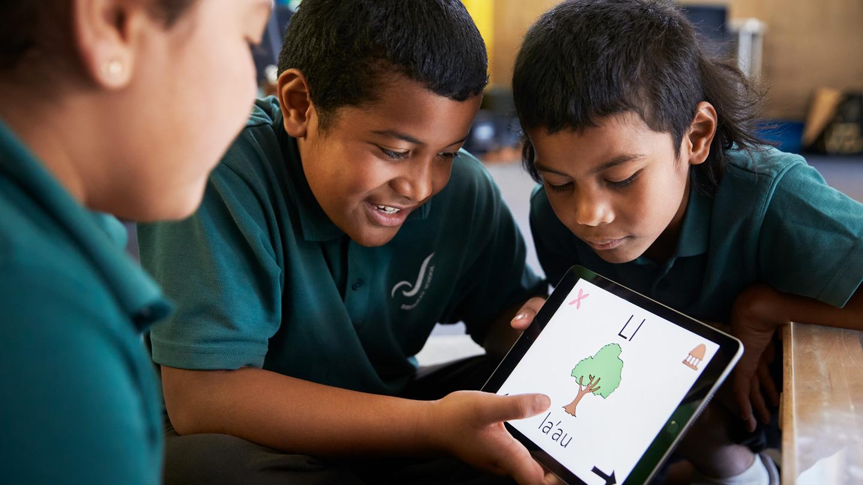Bromley School students Leonie Bradbrook, Talia Uasi, and Siosaia Uasi using iPad.