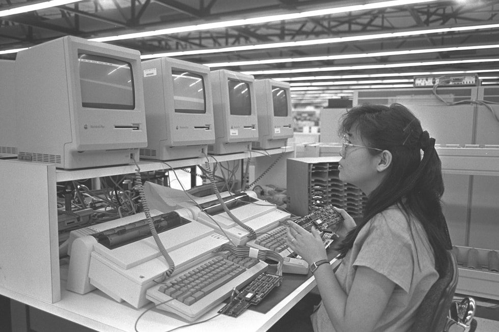 An Apple facility worker inspects machines from the Apple II series.
