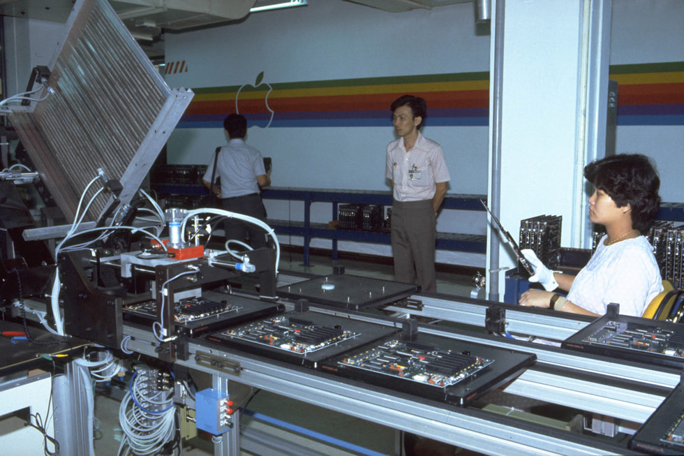 Facility workers in front of an assembly line for Apple IIe.