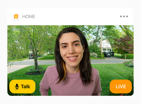 "View of a doorbell camera shows a woman in a pink sweatshirt. The words ""Talk"" and ""Live"" are on screen."